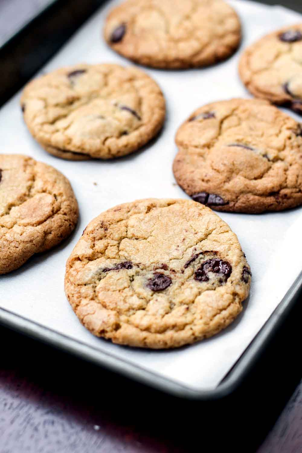 Baked chocolate chip cookies on a sheet pan lined with parchment paper