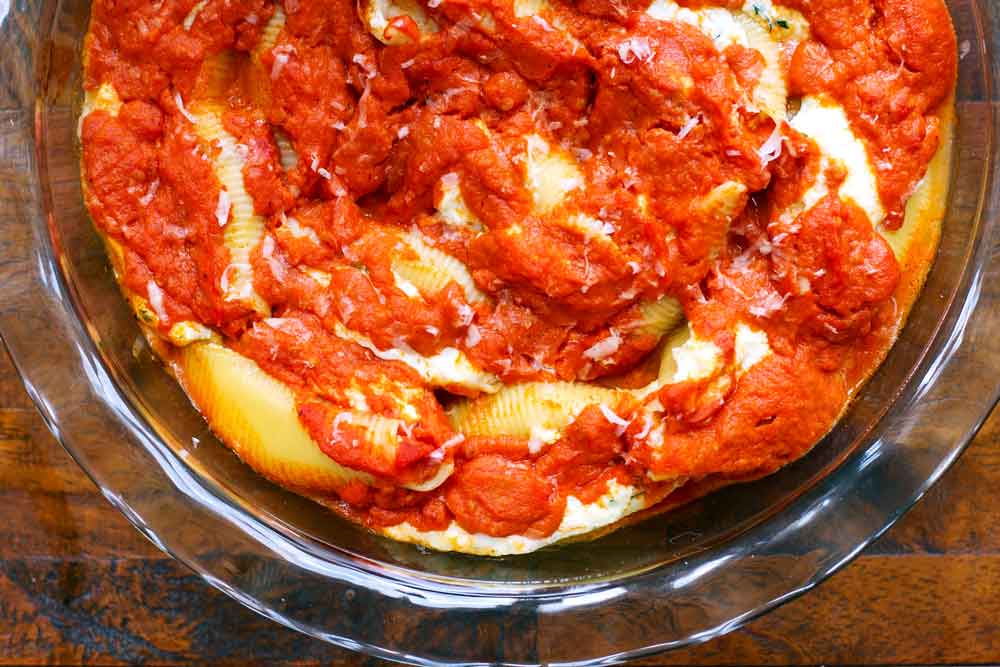 Stuffed shells in a clear pie dish topped with tomato sauce