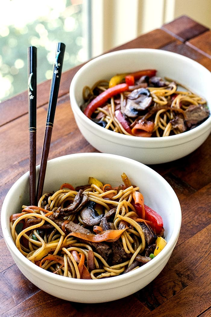 Two bowls of beef and veggie noodle bowls