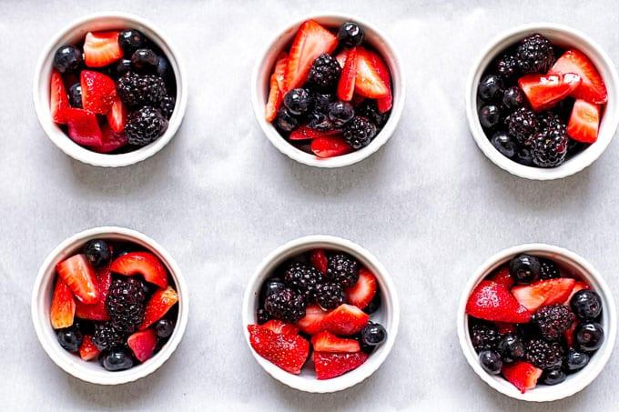 six ramekins filled with fresh berries