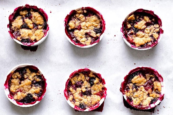 six berry crumbles on a sheet pan lined with parchment paper