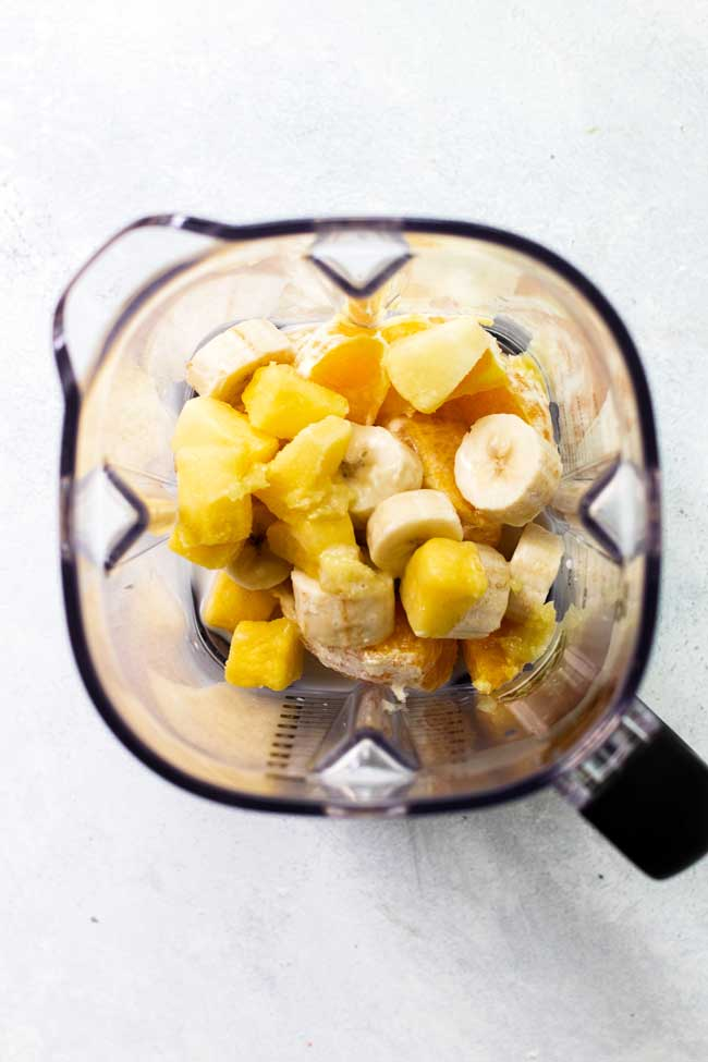 A blender filled with frozen bananas, pineapple, ginger, and orange segments