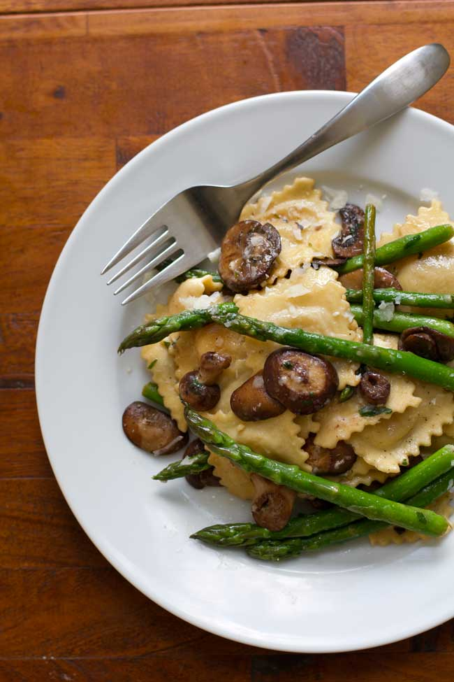 Ravioli with asparagus and mushrooms on a white plate with a fork