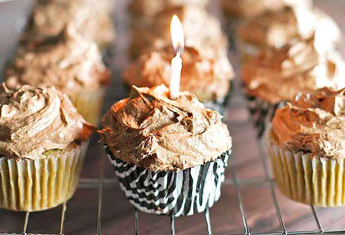 Coffee cupcakes with chocolate frosting on a baking rack with one cupcake with a lit birthday candle