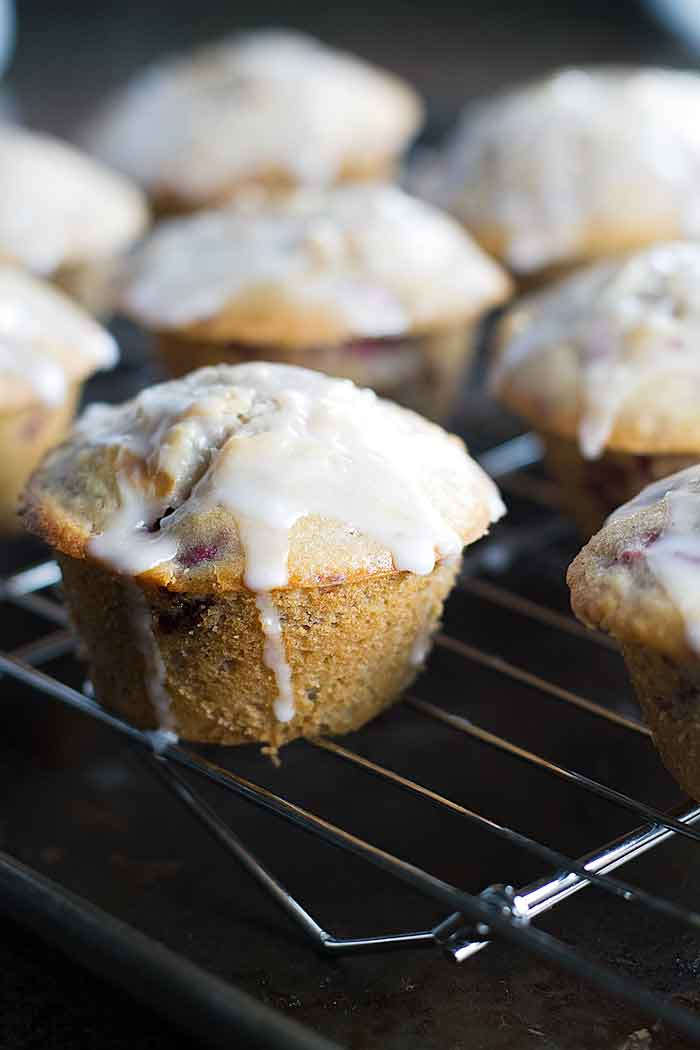baked raspberry muffins topped with a lemon glaze