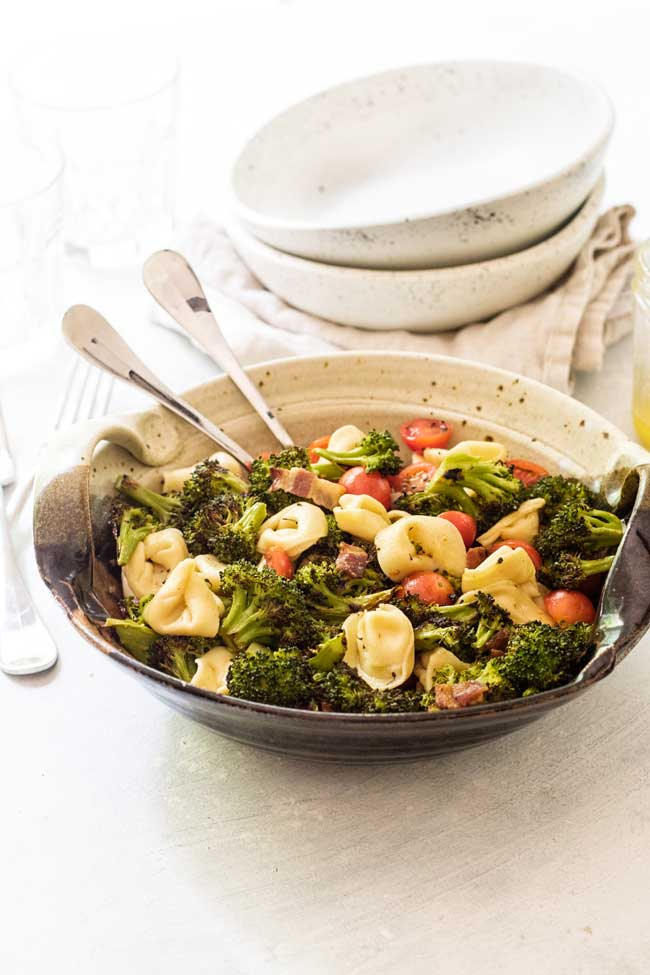 Tortellini Pasta Salad with Roasted broccoli in a bowl with two serving spoons