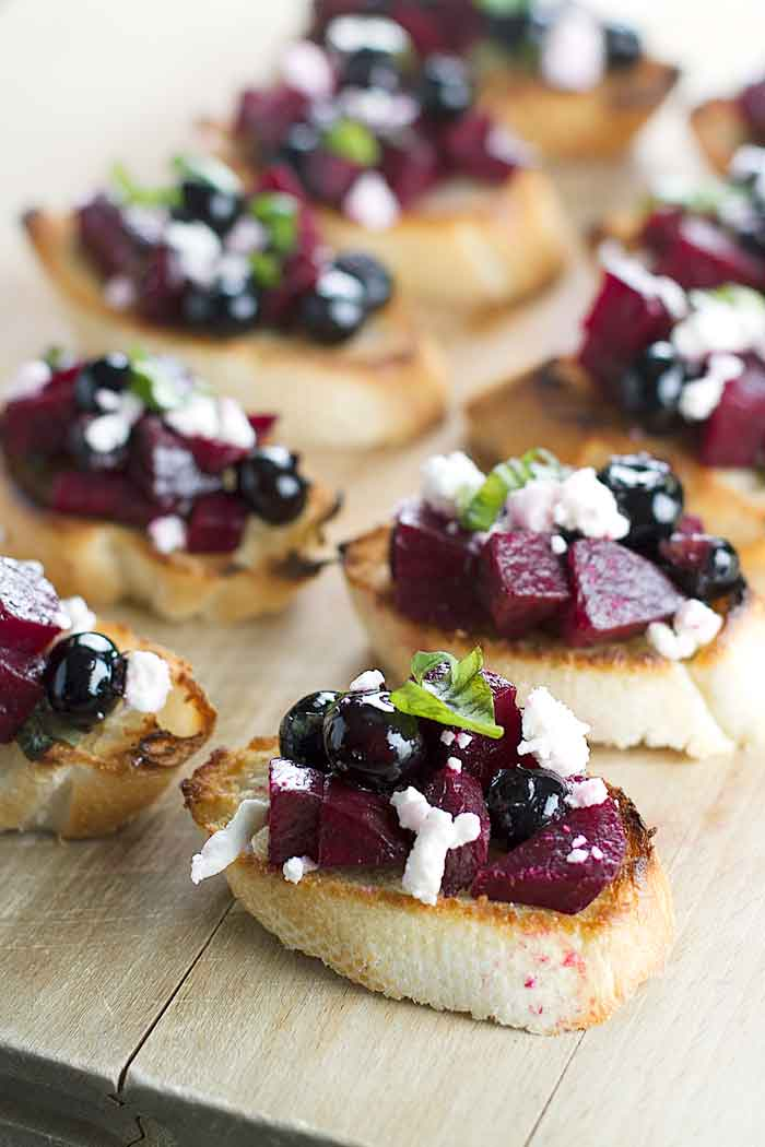 beet and blueberry bruschetta lined up on a cutting board