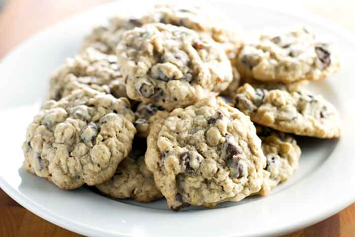 Oatmeal raisin cookies with chocolate chips on a white plate