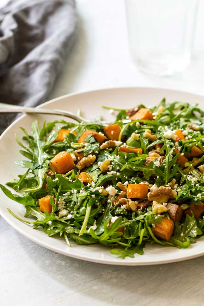 roasted sweet potato and arugula salad on a plate with a grey napkin and water glass in the background