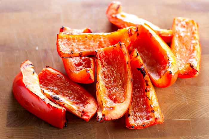Sliced grilled red bell peppers on a cutting board