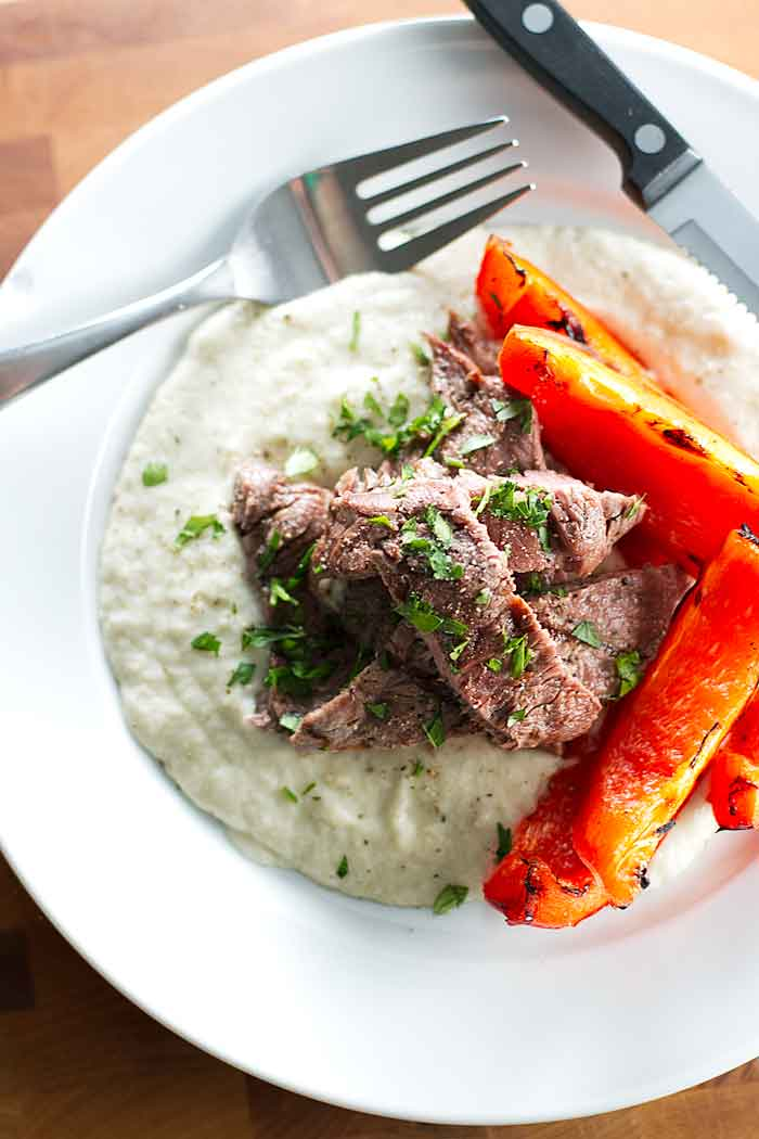 Eggplant puree, grilled steak, and bell peppers on a plate with a knife and fork