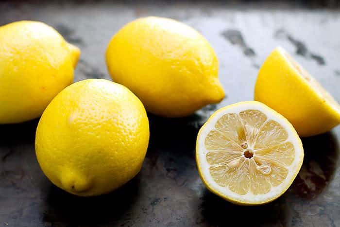 Fresh lemons on a sheet pan with one sliced in half