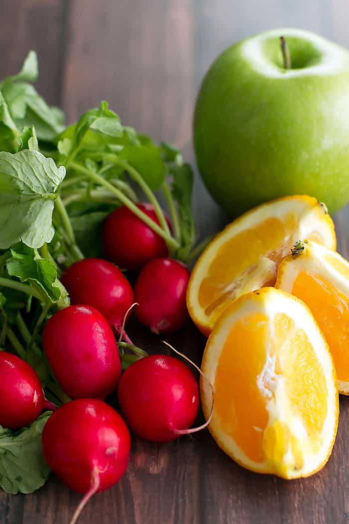 fresh radishes with orange segments and a green apple in the background