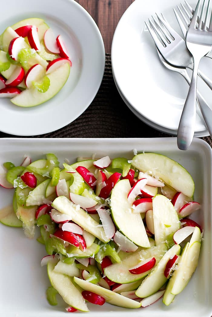 Radish and green apple salad in a dish with white plates and forks