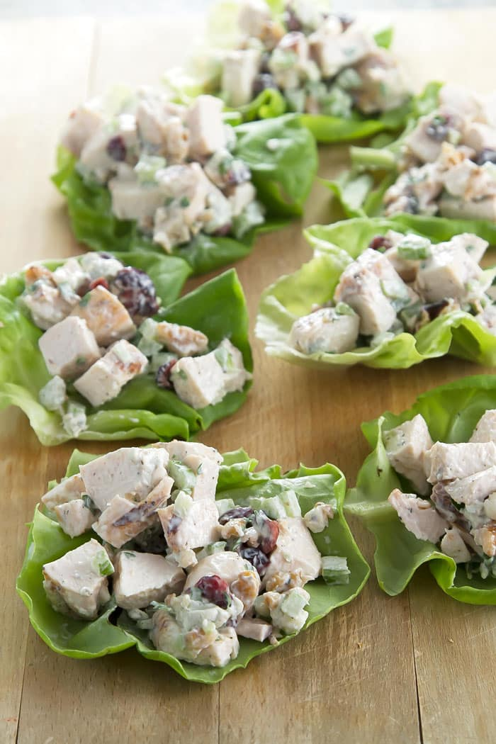chicken salad lettuce wraps lined up on a cutting board