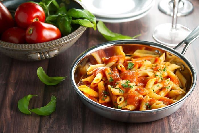 pasta with pomodoro sauce in a skillet with fresh tomatoes and basil in a bowl