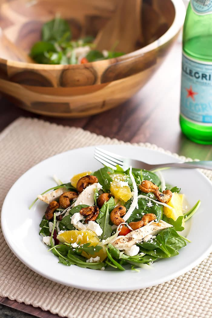 salad on a white plate with a fork and a bottle of water