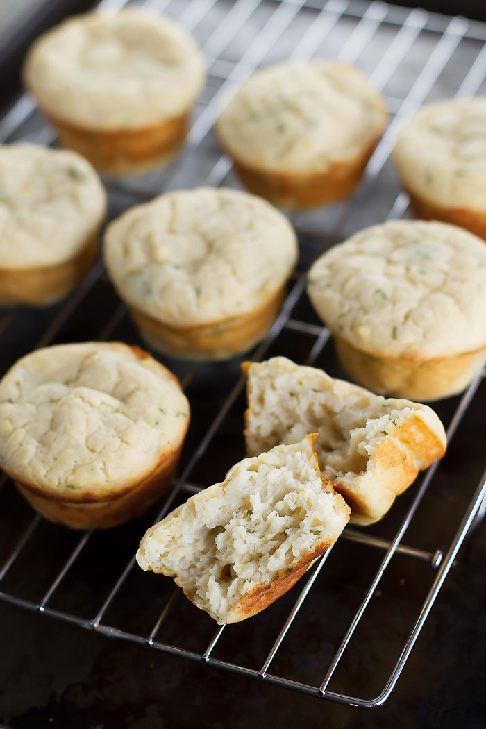 savory ricotta muffins on a baking rack with one muffin cut in half