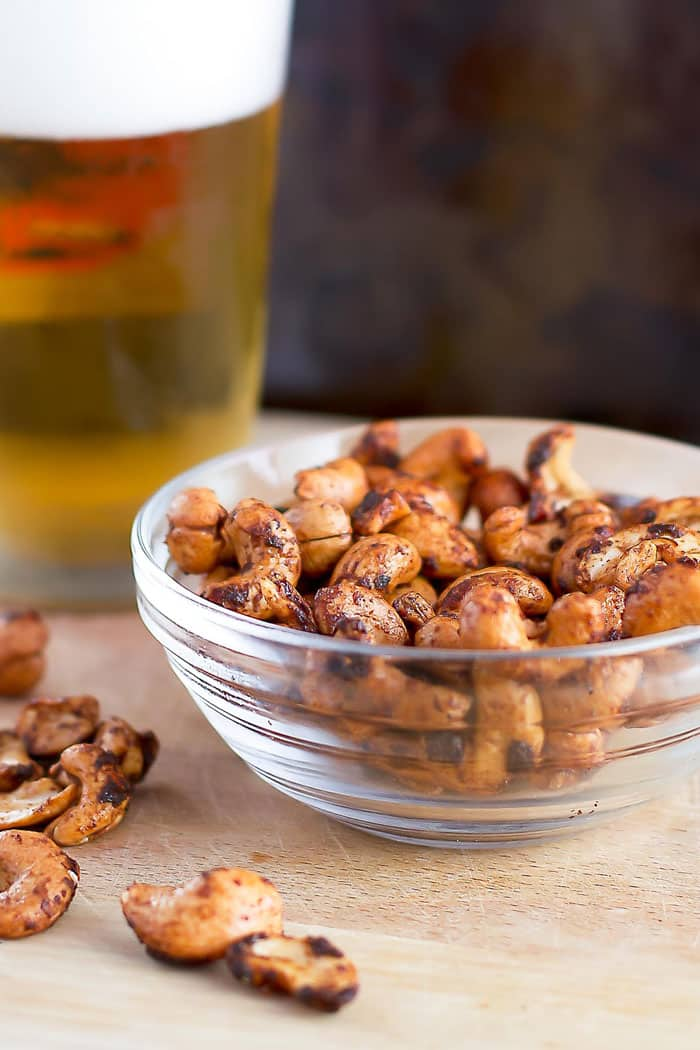 sweet and smokey cashews in a clear bowl with a beer