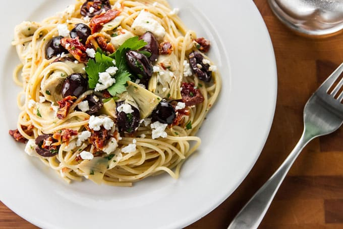 A quick and easy pasta dish with olives, artichoke hearts, sundried tomatoes, and creamy feta cheese - on the table in 15 minutes! | girlgonegourmet.com
