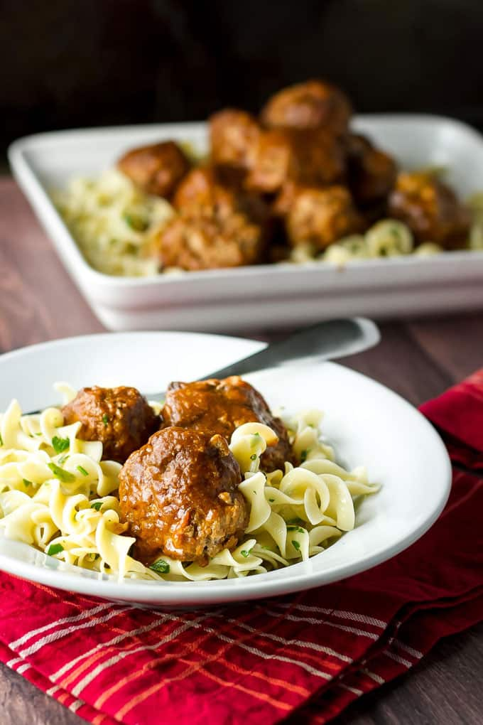 buttered noodles topped with braised meatballs in a white bowl