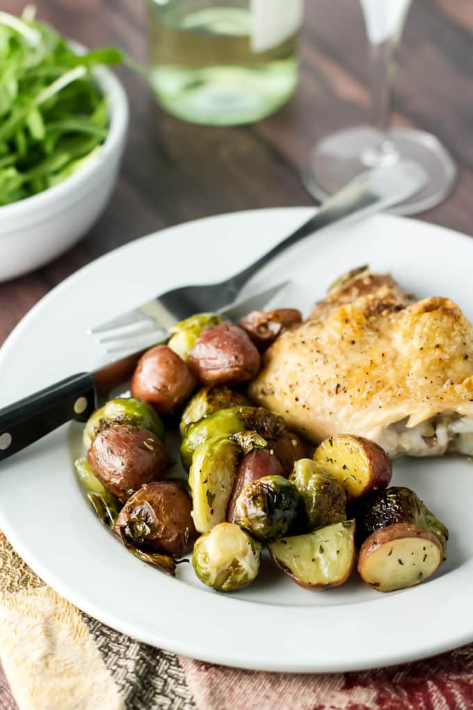 photo of a plate with roasted chicken thigh and veggies