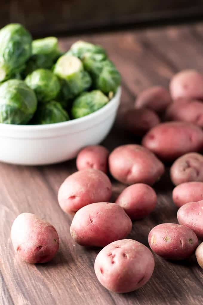 Photo of red potatoes with a bowl of brussels sprouts in the background