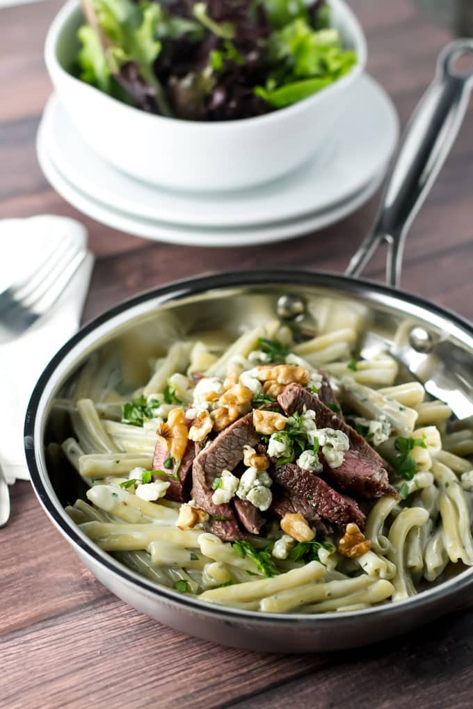 blue cheese pasta with steak in a skillet with a salad in the background