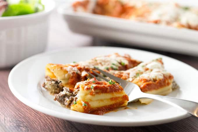 Baked cheesy beef manicotti on a white plate with a fork