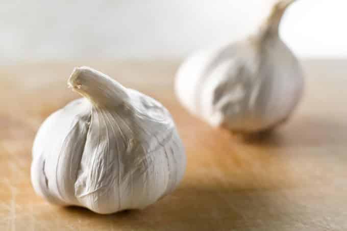 Two bulbs of garlic on a cutting board