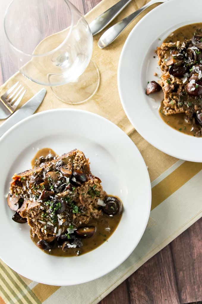 two plates with meatloaf topped with balsamic mushroom sauce