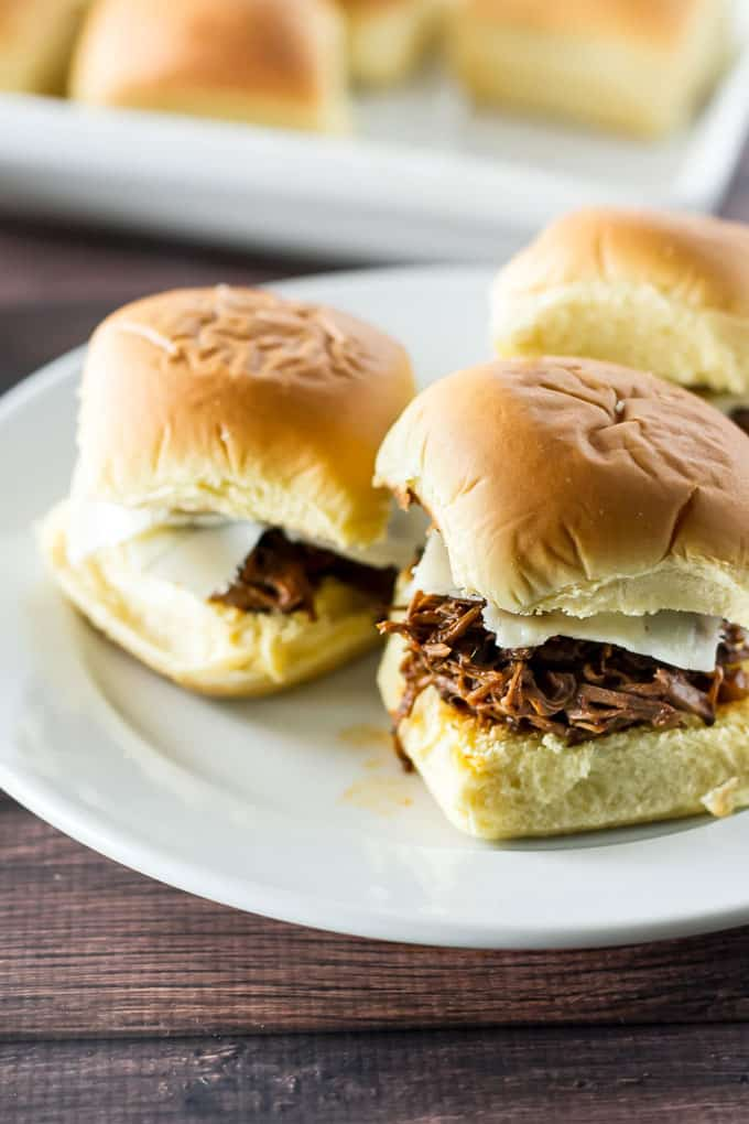 close-up photo of short rib sliders on a white plate