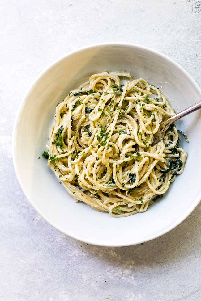 one serving of creamy goat cheese spaghetti in a white bowl with a fork