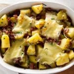 Tartiflette is a simple potato casserole with crispy bacon, creamy brie cheese, and fresh chives. Popular in the French Alps is a dish that will warm you through on the coldest of days | girlgonegourmet.com