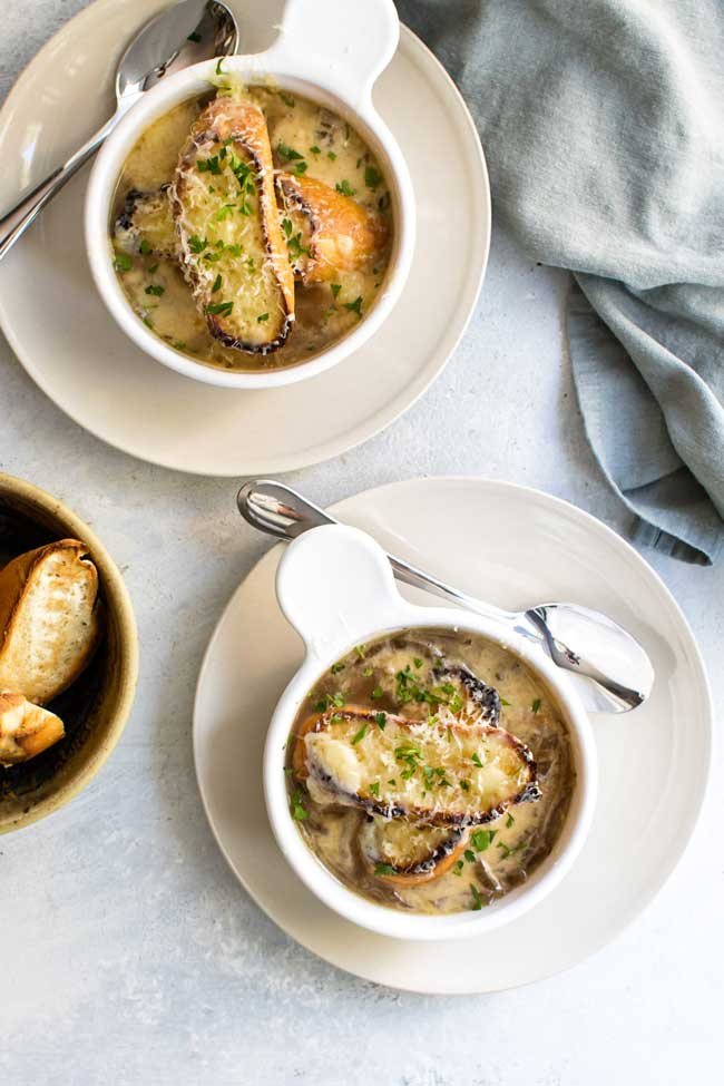 overhead photo of two bowls of French Onion soup topped with toasted bread and melted gruyere cheese