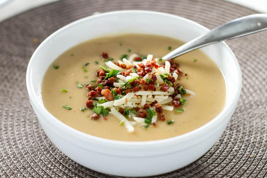 Potato Soup with Crispy Pancetta in a white bowl with a spoon