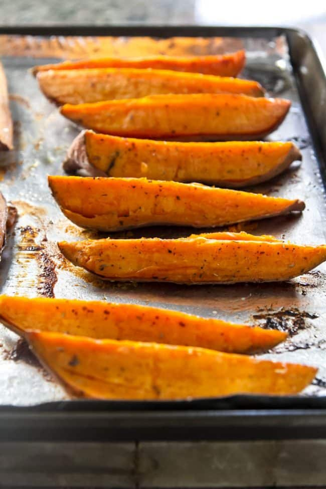 Roasted Sweet Potato Wedges lined up on a sheet pan