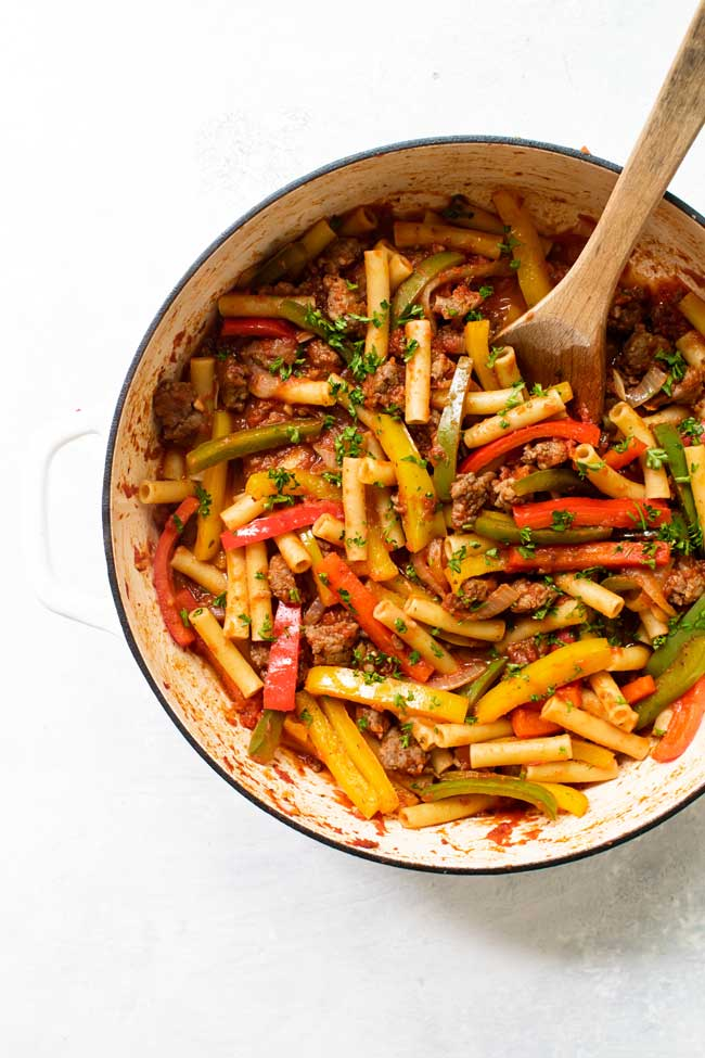 Italian sausage and peppers in a white pan with a wooden spoon