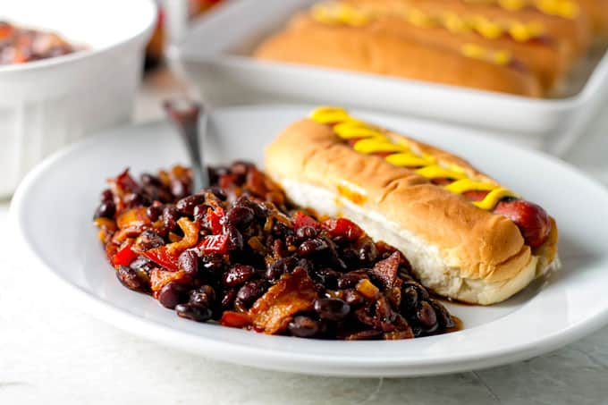 baked black beans on a white plate with a hot dog.