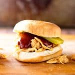 Shredded BBQ Chicken made in the slow cooker and served on buns with dill pickle slices | get more sandwich ideas! https://www.pinterest.com/april7116/burgers-sandwiches/