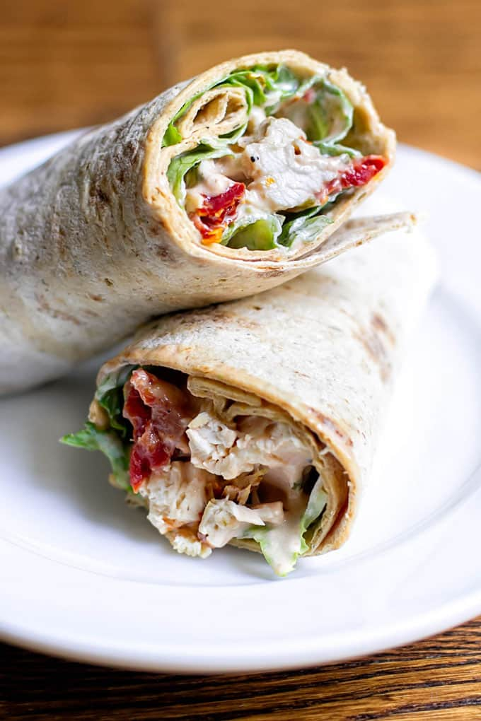 two sun-dried tomato chicken salad wraps stacked on a plate