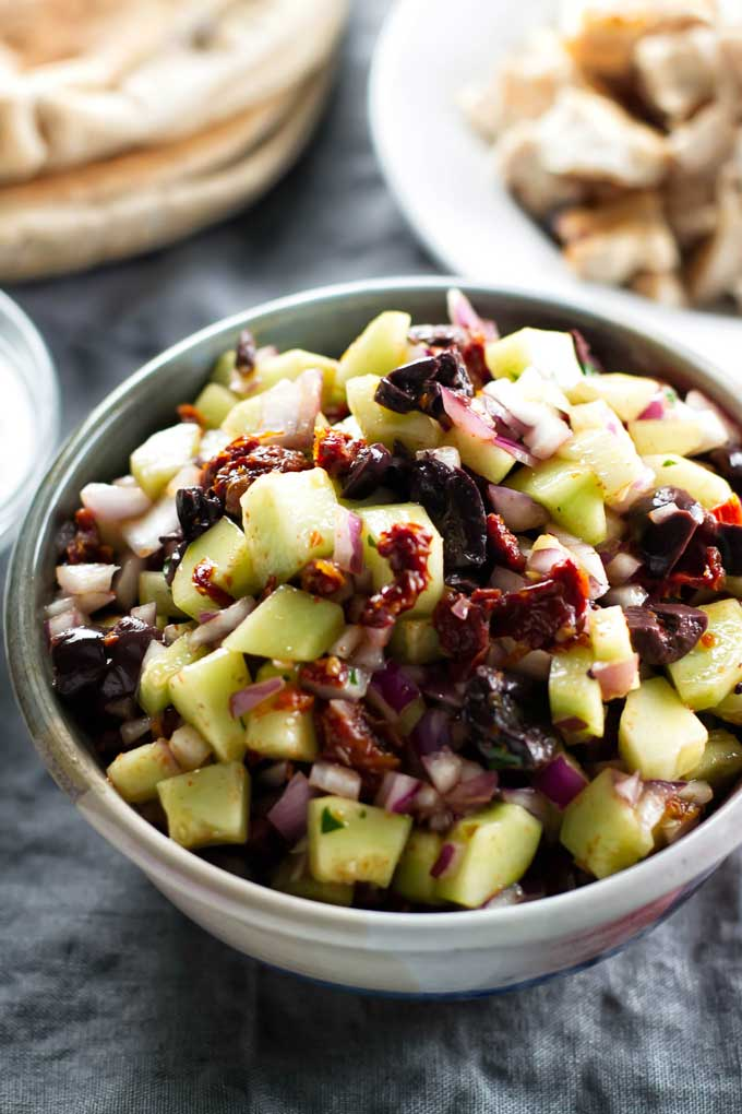 mixture of cucumbers, sun dried tomatoes, and olives in a bowl