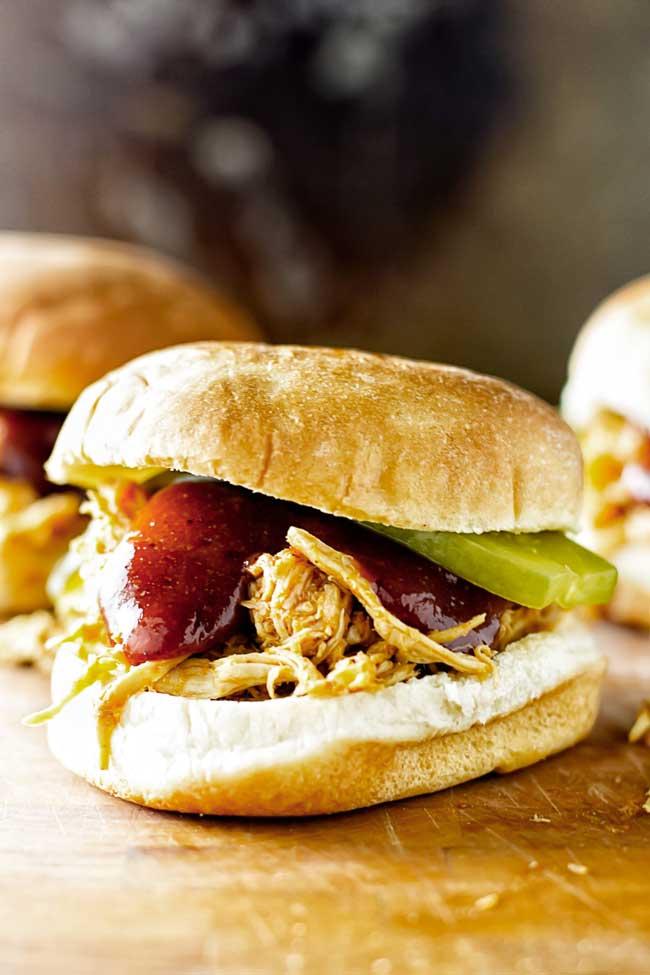 a shredded BBQ chicken sandwich on a cutting board