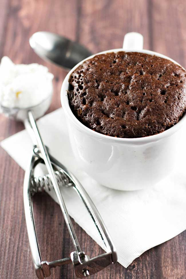 Molten Chocolate Mug Cake in a white mug with a scoop of ice cream on the side