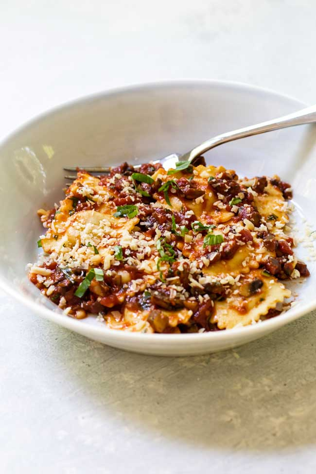 mushroom marinara tossed with cheese ravioli in a bowl with a fork