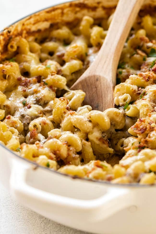 Creamy mushroom macaroni and cheese in a large pan with a wooden spoon
