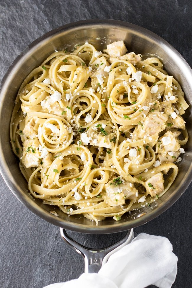 Tomatillo chicken pasta in a skillet with a white napkin around the handle