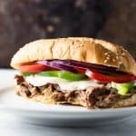 Slow Cooker Shredded Beef Sandwiches topped with melted provolone cheese and crisp bell pepper and red onions | girlgonegourmet.com
