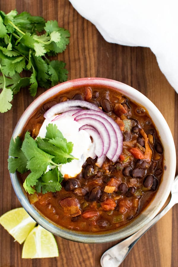 a bowl of black bean chili garnished with onions, sour cream, and fresh cilantro