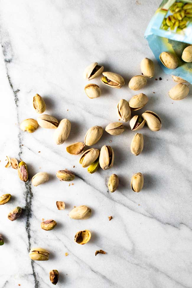 shelled pistachios on a marble board